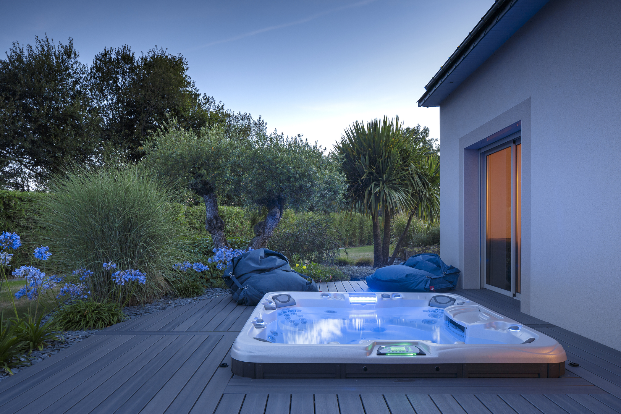 Outdoor in-ground hot tub installation in a deck surrounded by greenery.